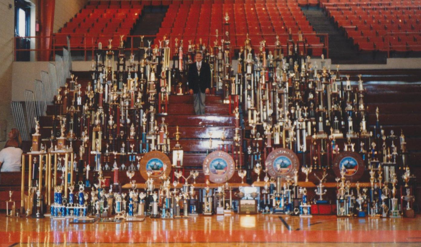 Dr. Ric Best surrounded by trophies won by bands under his direction.